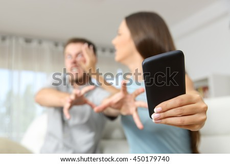 Angry couple or marriage fighting for a mobile phone at home - stock photo