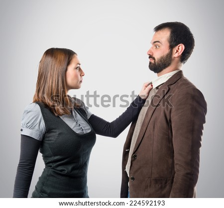 Angry couple over grey background