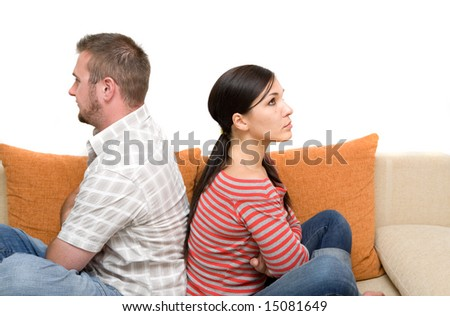 angry couple sitting on sofa - stock photo