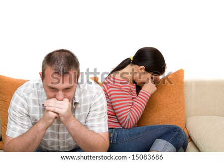 angry couple sitting on sofa - stock photo