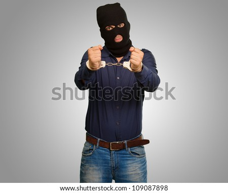 angry criminal man locked in handcuffs isolated on a grey background