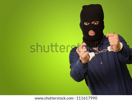 angry criminal man locked in handcuffs isolated on green background