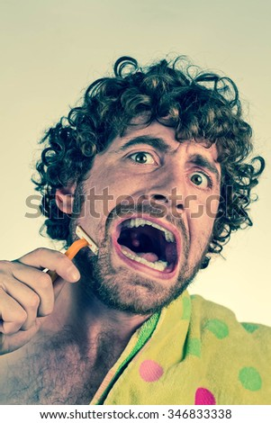 Angry curly haired man shaves off his beard - stock photo