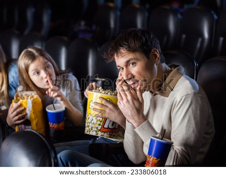 Angry daughter giving shh expression to father using mobilephone in movie theater - stock photo