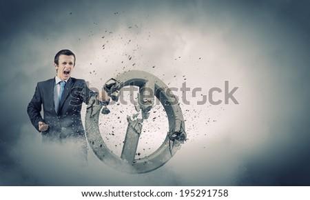Angry determined businessman crashing stone prohibition symbol - stock photo