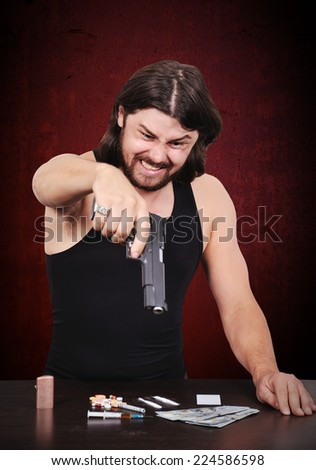 angry drug dealer with gun on red background - stock photo