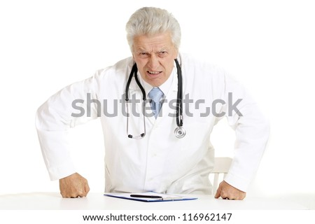 angry elderly doctor at a table on a white background