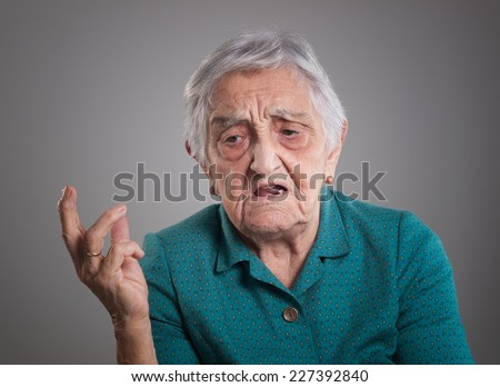 Angry elderly woman isolated on dark background - stock photo
