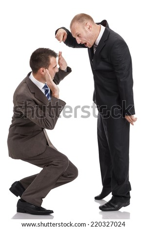 Angry employer in a dark suit shouting at a crouched employee in a brown suit, isolated on white - stock photo