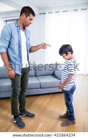 Angry father scolding his son in living room at home - stock photo
