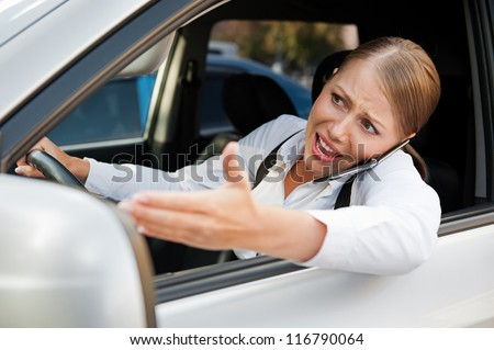 angry female driving the car, holding the mobile phone and screaming at someone - stock photo