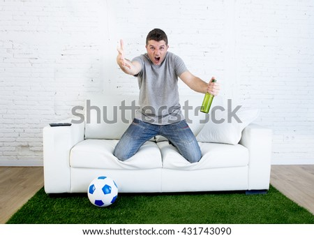 angry football fanatic fan watching game on television holding beer gesturing upset and crazy angry complaining and screaming  at home couch on grass carpet with ball emulating stadium pitch - stock photo