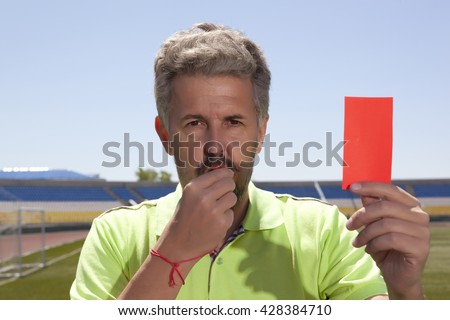 Angry football referee blowing a whistle and pointing with his hand - stock photo