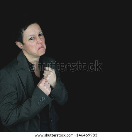 angry, frustrated businesswoman in suit, with fists raised ready for a fight. Black background with copy space.