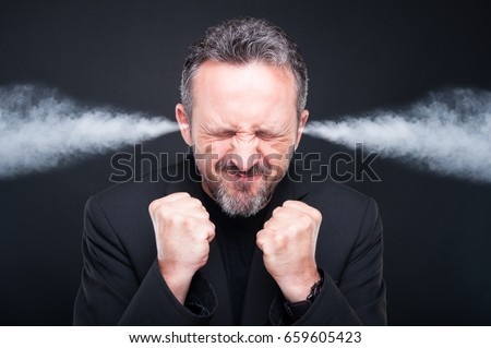 Angry frustrated man with exploding head and steam coming out of his ears on dark background