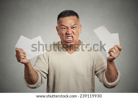 Angry frustrated middle aged man tearing business documents to pieces isolated on grey wall background. Negative human emotions, face expression, feelings, crisis - stock photo
