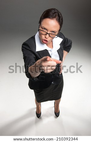 Angry funny businesswoman isolated on grey background. furious woman looking and pointing up at camera - stock photo