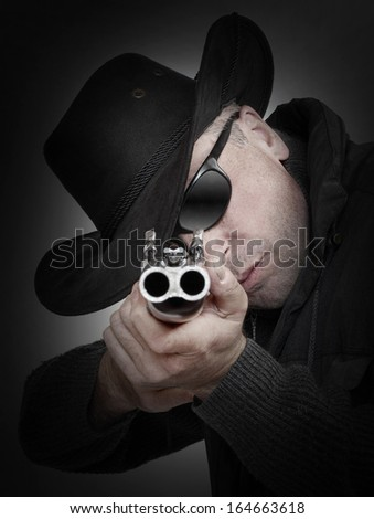 Angry gangster with shotgun aiming at you. Gun control concept.  - stock photo