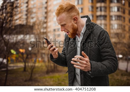 Angry ginger man screaming on phone outdoor - stock photo