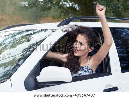 angry girl driver inside car, look into the distance, has emotions and waves, summer season