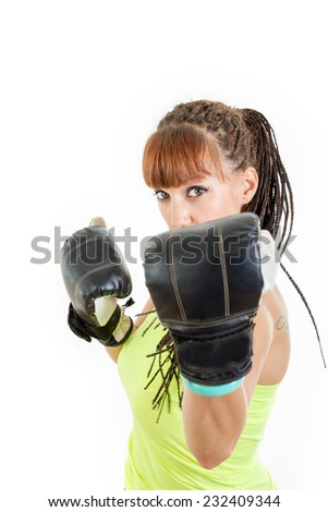 Angry girl in rage wearing boxing gloves ready to fight and standing in combat position and trying to defend herself. Strength, power or competition concept image of beautiful young caucasian woman - stock photo