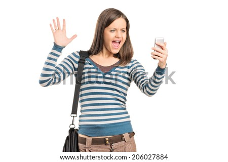 Angry girl looking at a cell phone isolated against white background - stock photo