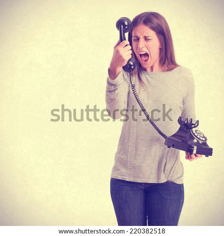 Angry girl with a telephone - stock photo