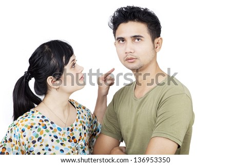 Angry girlfriend pointing at boyfriend on white background