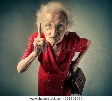 Angry grandma pointing out something  - stock photo