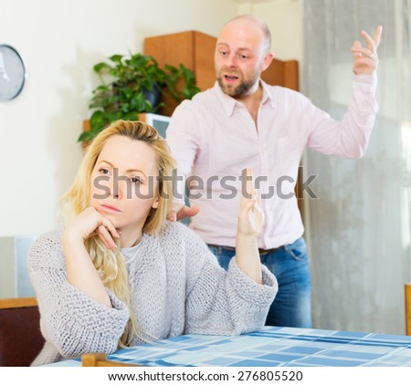 Angry guy and sad woman during quarrel in living room at home - stock photo