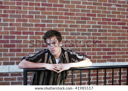 angry handsome teen boy by brick wall