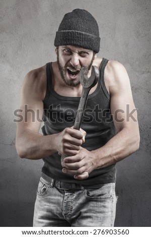 Angry hooligan or thug shouting a threatening with a raised wrench during a violent crime or mugging over a grey background