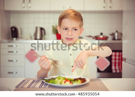 Angry hungry boy child complains about the food on the table