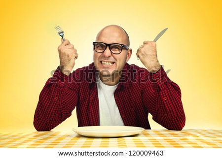 Angry Hungry Man Sitting at Dinner Table with Fork and Knife Raised.