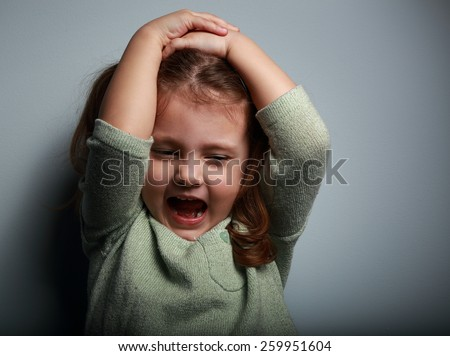 Angry kid girl shouting with open mouth and holding hands the head on dark background - stock photo