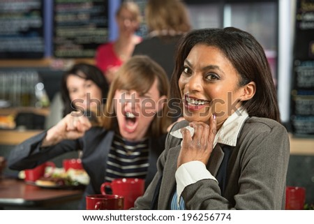 Angry lady behind giggling woman in coffee house - stock photo