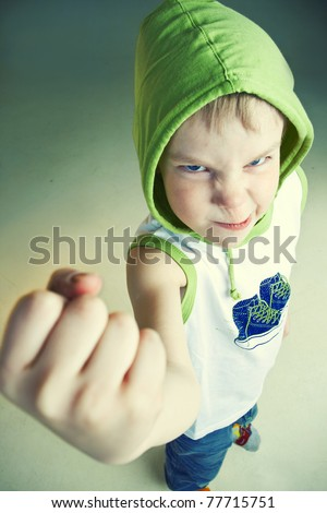 Angry little boy with fist - stock photo