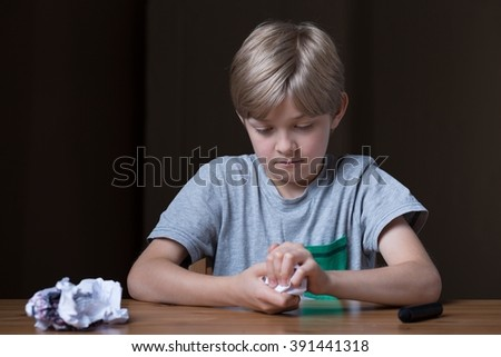 Angry little child at the table destroying his drawing - stock photo