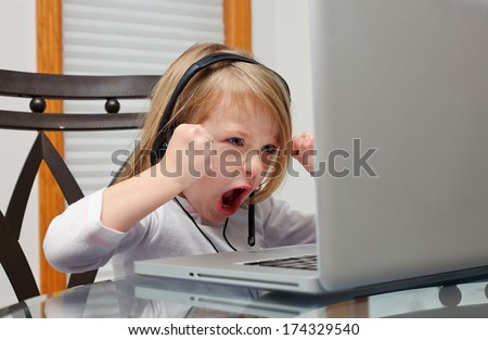 Angry little girl in headphone  sitting at the table with laptop - stock photo