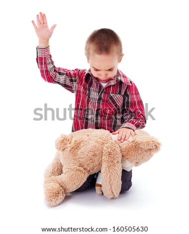 Angry little kid beating his teddy bear - domestic abuse concept - stock photo