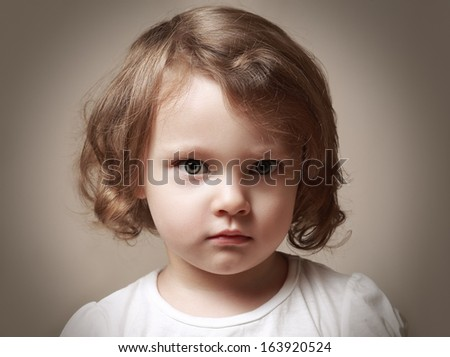 Angry little kid girl portrait looking. Closeup - stock photo