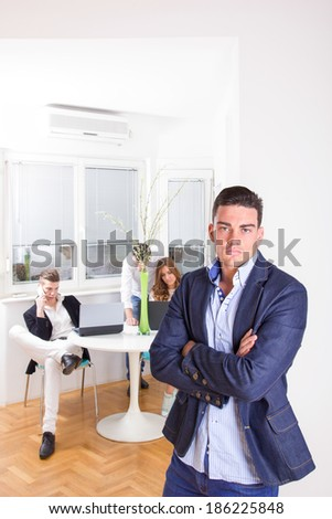 angry lonely business man pouting posing standing in front of colleagues working as team - stock photo