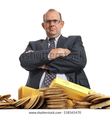 Angry looking man and a pile of gold - stock photo