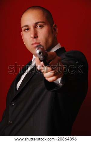 Angry looking man pointing a gun at the camera. Red background to symbolize danger. - stock photo