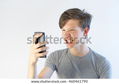 Angry looking teenager screaming at his phone.