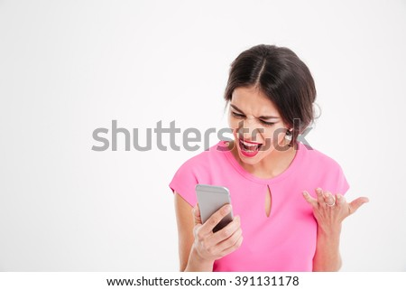 Angry mad young woman shouting and using mobile phone over white background - stock photo