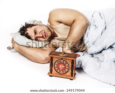 angry man and alarm clock in bedroom - stock photo