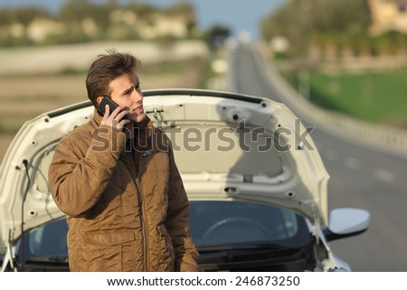 Angry man calling roadside assistance for his breakdown car in a road in winter - stock photo