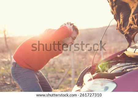 Angry man checking his car. Corrupt car on the road - stock photo