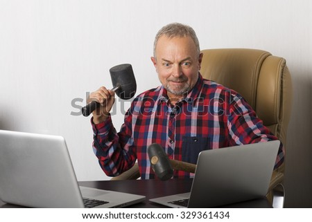 Angry man crashing laptop with a hammer